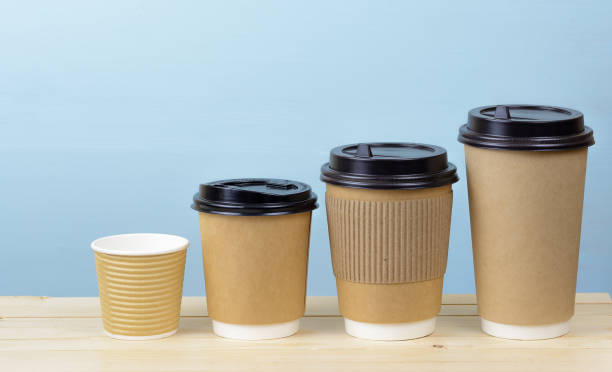 paper coffee cups on a wooden table - paper coffee cup stock photos and pictures