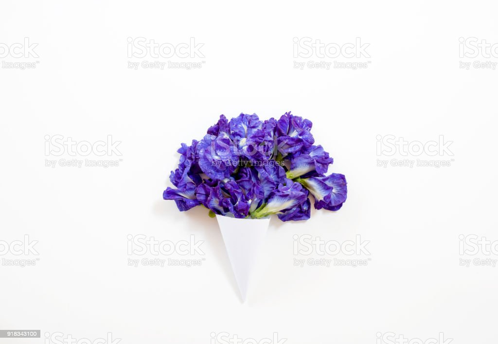 paper cone with Butterfly pea or blue pea bouquet on white background. Flat lay, top view stock photo