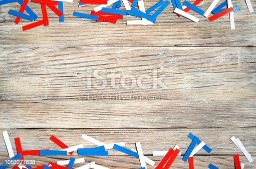 970809318 istock photo Paper confetti of national colors of France, Russia, USA, Serbia white-blue-red on a white wooden background, the concept of independence day and national holidays 1053277838