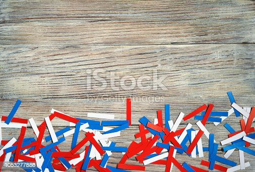 970809318 istock photo Paper confetti of national colors of France, Russia, USA, Serbia white-blue-red on a white wooden background, the concept of independence day and national holidays 1053277886