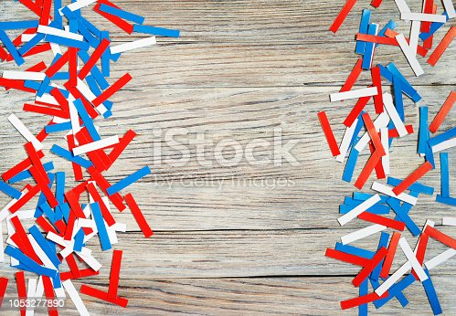 970809318 istock photo Paper confetti of national colors of France, Russia, USA, Serbia white-blue-red on a white wooden background, the concept of independence day and national holidays 1053277890