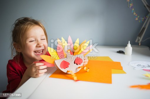 paper craft for kids. DIY Turkey made for thanksgiving day. create art for children. girl playing with a toy.