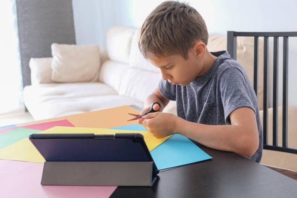 Papier Handwerk für Kinder. Kind schneidet farbiges Papier mit Schere. Junge suchen Video-Tutorial und machen Papier Handwerk Projekt zu Hause – Foto