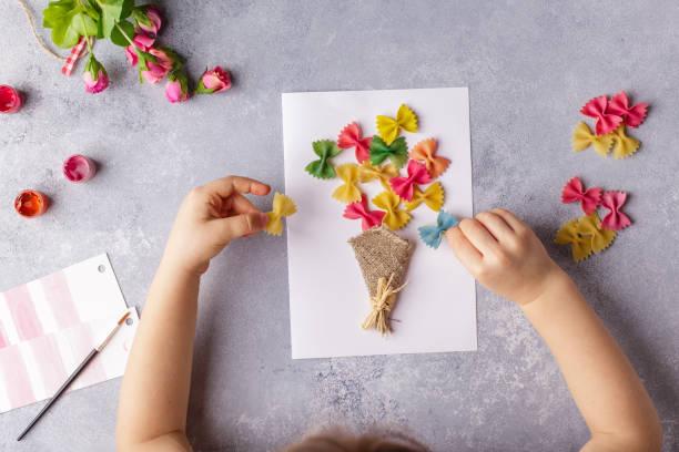 papierhandwerk für muttertag, 8 märz oder geburtstag. kleines kind macht einen blumenstrauß aus farbigem papier und farbigen nudeln - handgemacht stock-fotos und bilder