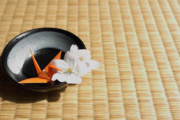 grou de papel dobrado e cereja flores no tatame tradicional japonês - cherry blossoms imagens e fotografias de stock