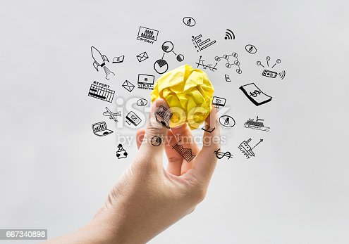 Yellow paper crumpled ball on human hand with business icons.Idea concepts