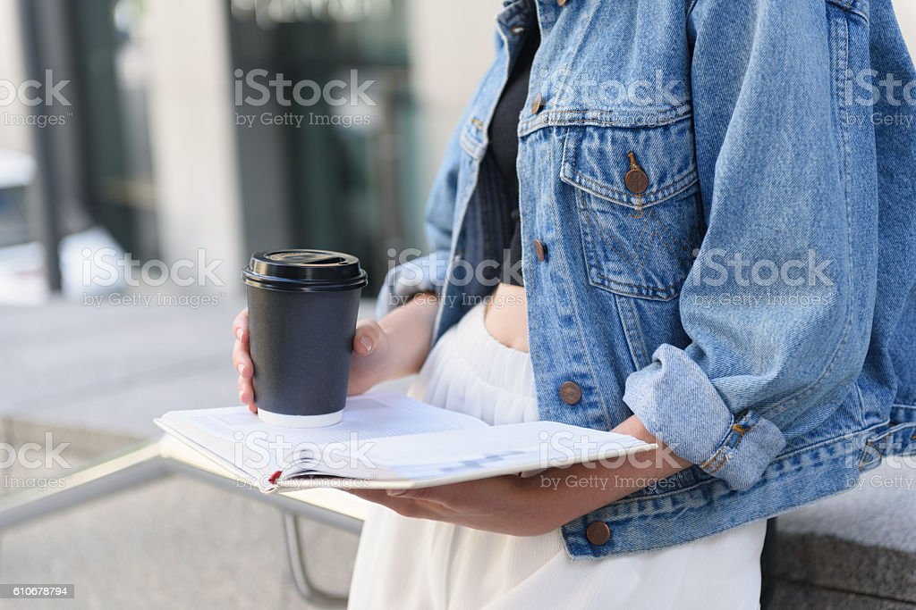 paper cup and journal in student hands stock photo