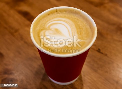 Paper cup of cafe latte on wooden table background. Art style hot coffee. A latte is a coffee drink made with espresso and steamed milk.