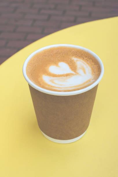 Papierbecher Kaffee auf gelbem Tisch mit Kopierplatz. – Foto