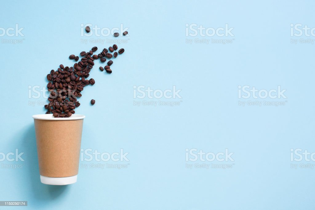 Paper cup of coffee with coffee bean on blue background. Copy space