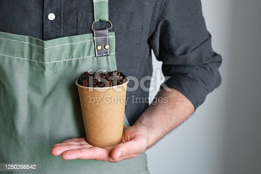 istock A paper cup with coffee beans in the hands of a barista. Ready to brew roasted coffee. A man in a culinary apron. Fresh organic coffee. Disposable paper cup. Making coffee, professional service 1250266542