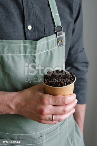 istock A paper cup with coffee beans in the hands of a barista. Ready to brew roasted coffee. A man in a culinary apron. Fresh organic coffee. Disposable paper cup. Making coffee, professional service 1250266544