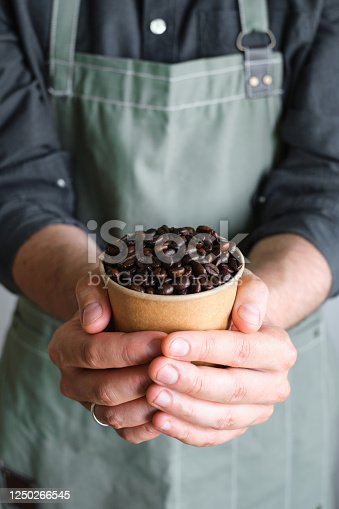 istock A paper cup with coffee beans in the hands of a barista. Ready to brew roasted coffee. A man in a culinary apron. Fresh organic coffee. Disposable paper cup. Making coffee, professional service 1250266545