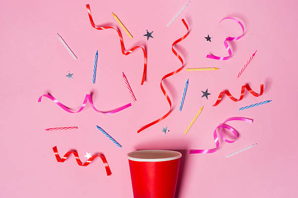 paper cup with colorful party streamers on pink background. - geburtstagsgratulation stock-fotos und bilder