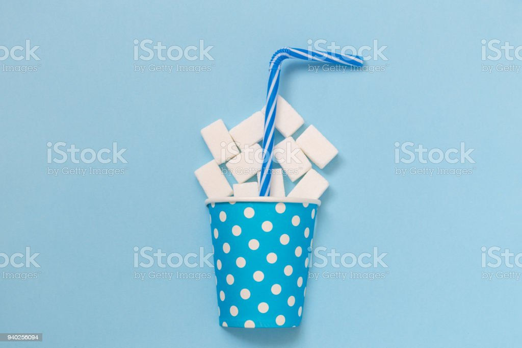 Paper cup with sugar cubes and drinking straw isolated on blue minimalistic concept. royalty-free stock photo