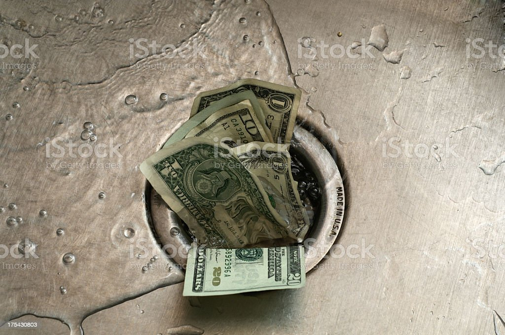 US paper currency, shoved in to the drain of a wet sink  stock photo