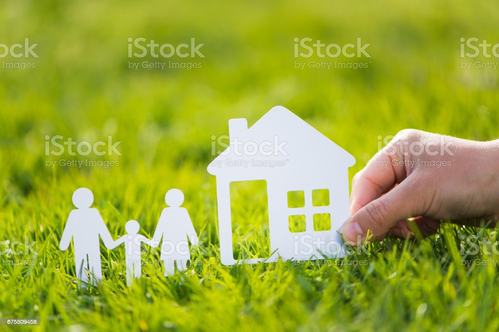 Paper cut family with house in green grass background photo libre de droits