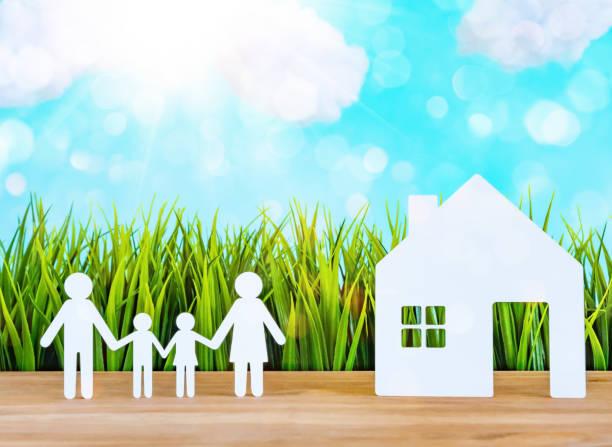 papierschnitt der familie mit grünem grashintergrund - eco bastelarbeiten stock-fotos und bilder
