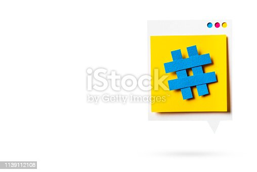 istock Paper cutout of hashtag symbol on a yellow speech bubble isolated. Concept of social media and digital marketing. 1139112108