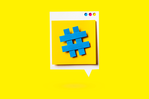 istock Paper cutout of hashtag symbol on a yellow speech bubble on yellow background. Concept of social media and digital marketing. 1139349423