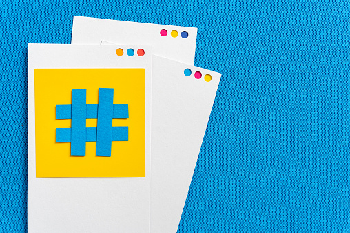 istock Paper cutout of hashtag symbol with mobile device concept made with paper on a blue textured background. Concept of social media and digital marketing. 1166523035