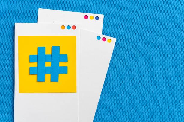 papierausschnitt des hashtag-symbols mit mobilem gerätekonzept mit papier auf blauem strukturiertem hintergrund. konzept von social media und digitalem marketing. - instant messaging stock-fotos und bilder