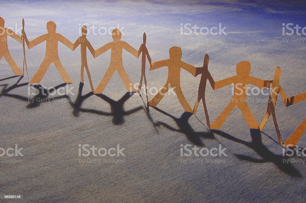 Paper cutout of people holding hands placed on a wood table - Royalty-free Assistance Stock Photo