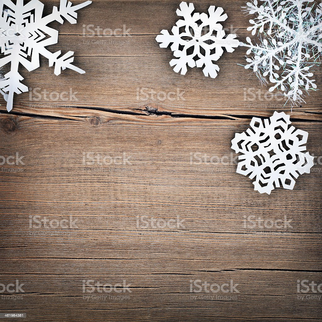Paper cutout style snowflakes on a wooden background stock photo