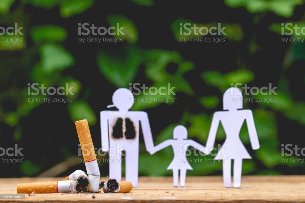 Bonecas de papel, os pais e filha. Boneca de papai ter queimado os pulmões. As mãos de mãos dadas com sua filha. Lá são queimadas bitucas de cigarros. - foto de acervo