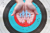 istock Paper family in hands on archery target background 1270382269