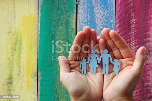 istock Paper family in hands on wooden coloured background welfare concept 855470536