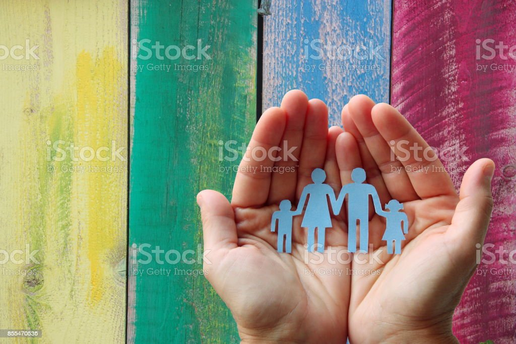 Paper family in hands on wooden coloured background welfare concept stock photo