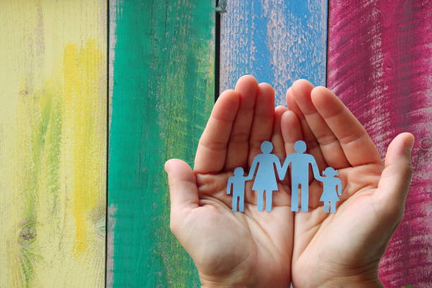 paper family in hands on wooden coloured background welfare concept - protezione foto e immagini stock