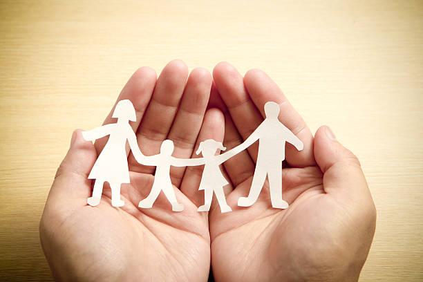 Papier-Familie in der Hand mit Holz Textur Hintergrund – Foto
