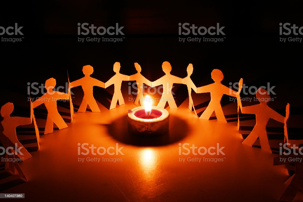 Paper figures forming a circle around a candle royalty-free stock photo