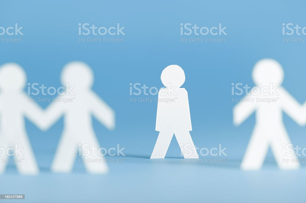 Paper figures holding hands with one alone not participating stock photo