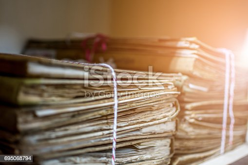 istock Paper files in a folder is a old documents or old letter it's a age-old and ancient archiving by stacking up in a documents paper shelf messy order 695068794