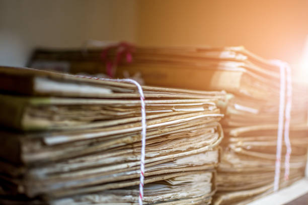 Paper files in a folder is a old documents or old letter it's a age-old and ancient archiving by stacking up in a documents paper shelf messy order stock photo