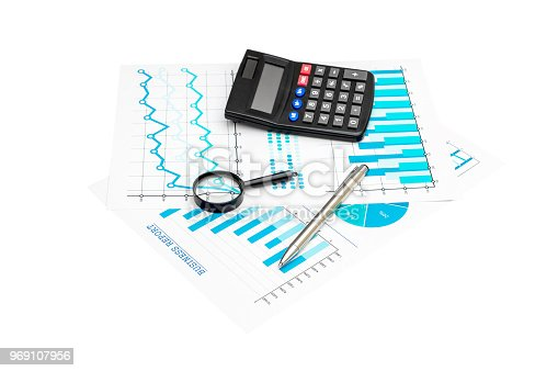 istock Paper financial graphs and charts with calculator, magnifying glass and pen isolated on white. 969107956