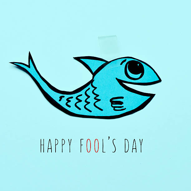 paper fish and text happy fools day a handmade paper fish attached with adhesive tape and the text happy fools day on a blue background april fools day stock pictures, royalty-free photos & images