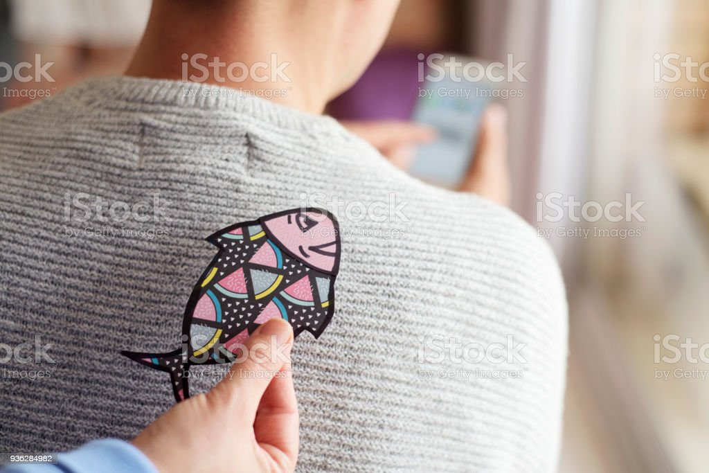 paper fish in the back of man for april fools day stock photo