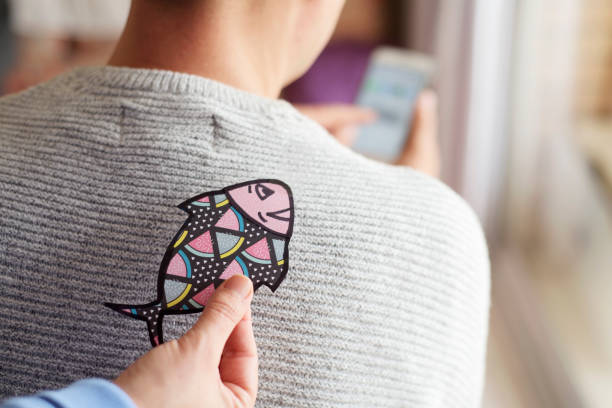 paper fish in the back of man for april fools day - april fools stock photos and pictures