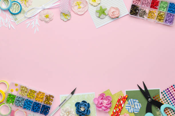 Paper flowers, tools, paper and scrapbooking items on pink background