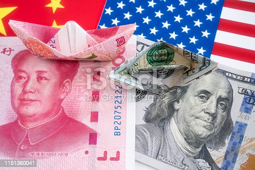 istock Paper folding ship of Dollar and Yuan currency 1151360041