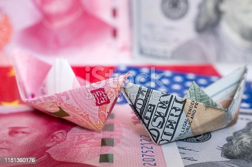 Paper folding ship of Dollar and Yuan currency