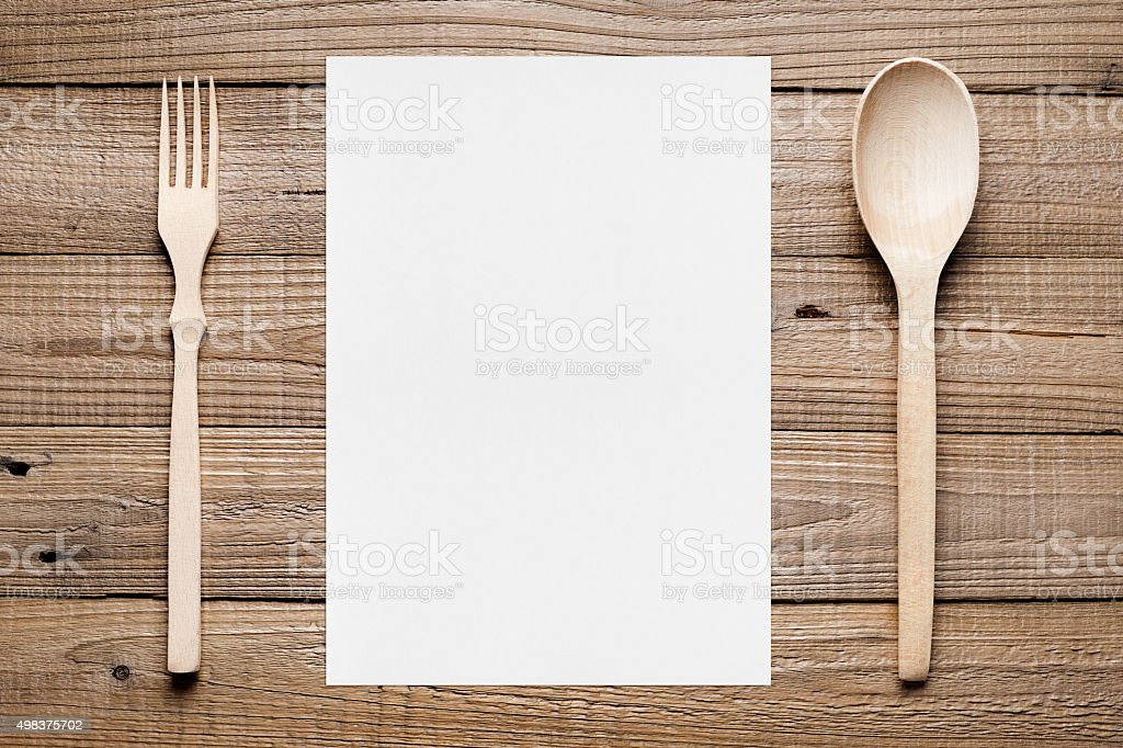 Paper for menu and wooden fork and spoon stock photo