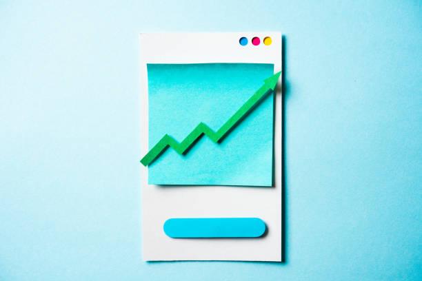 papier grüner pfeil auf smartphone und blau hintergrund aufgewachsen. wachstum-geschäft-graph-diagramm, börse handel und trends anlagekonzept. - popup cards stock-fotos und bilder
