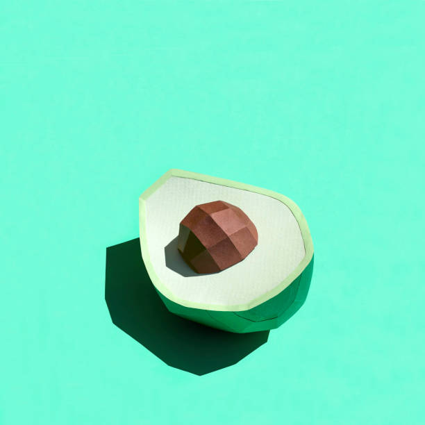 Paper half avocado with seed in bright sunshine stock photo