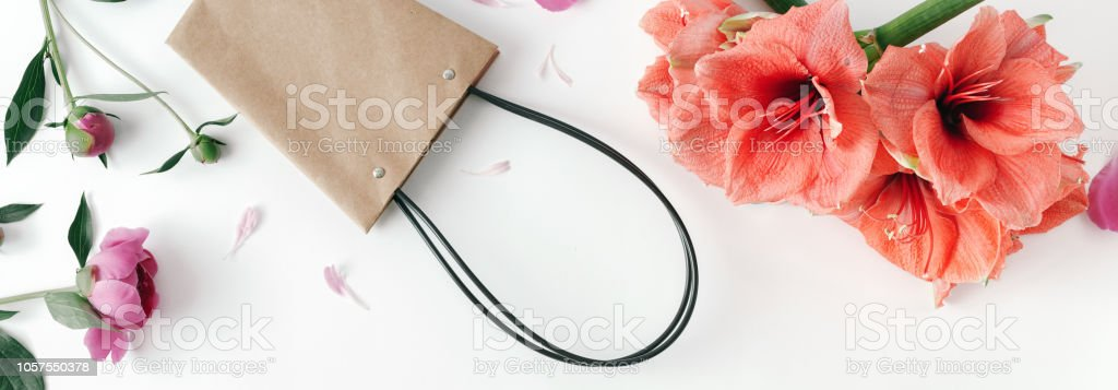 Paper hand bag with flowers amaryllis and peonies on white background...