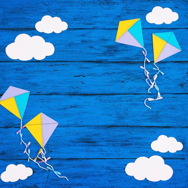 Papierhandwerk: Wolken und Drachen auf blauem Holzhintergrund – Foto